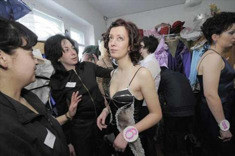 Hücrelerinden çıkan kadınlar, rengarenk kostümler içinde gardiyanlar eşliğinde podyuma çıktı.