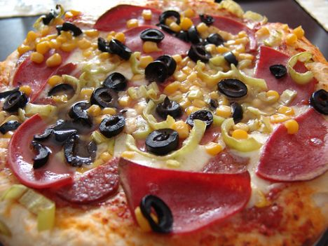 Karışık pizza (1 tepsi)   Malzemeler:  PEYNİRLİ MALZEME  200 gr küp doğranmış domates  Tuz, karabiber  3 domates  2 çorba kaşığı kekik  80 gr siyah çekirdek  Fesleğen  300 gr kaşar peyniri  KARİDESLİ MALZEME  1 limon  200 gr karides  300 gr kabak  4 çorba kaşığı zeytinyağı  1 yumurta  1-2 çorba kaşığı sirke, tuz, karabiber  1 enginar (hazır ürün, konserve)  6 kahve fincanı rendelenmiş kaşar peyniri  100 gr süt kreması  Hazırlanışı: Peynirli malzeme için domateslerin çekirdeklerini ayıkladıktan sonra ince dilimler halinde doğrayın. Peynirinin üçte birini küp küp doğrayın. Kalanı rendeleyin. Rendelenmiş peynirin yarısını, küp küp doğradığınız peynir ile karıştırın. Karidesli malzeme için limonun kabuğunu rendeleyip suyunu sıkın. Suyun yarısını karideslerin üzerine dökün.  Kabağı ince dilimler halinde doğrayın. Yağı kızdırıp kabakları kızartın. Sirkeyi ekleyin, Enginarı ikiye veya dörde bölün. Süt kremasını yumurtayla çırpın. Limon suyu, tuz ve karabiberle tatlandırın. Hazırladığınız hamurun yarısına süt kremalı karışımın üçte birini sürün. Karides, kabak ve enginarı üzerine yerleştirin. Kalan süt kremalı karışımı üzerine dökün. Doğranmış domatesi hamurun kalan yarısına yayın. Peynirli karışımı, dilimlediğiniz domatesleri ve zeytinleri ekleyin. Baharatları serpip peyniri ilave edin. Fırını 225 dereceye ayarlayıp ısıtın. Pizzayı fırının alt bölmesinde 25 dakika pişirin.