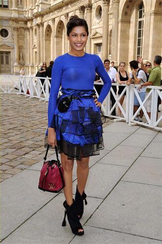 Freida Pinto – Louis Vuitton Podyumda siyah şifon bir gömlek ile kombinlenen fırfırlı elektrik mavisi eteği, Freida Pinto aynı tondaki penye bluzu ile kombinlemiş.