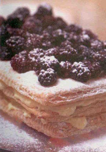 """Mutlu son(2 kişilik)  Malzemeler:  1 paket rulo milföy hamuru  Yarım kg dondurulmuş ya da taze kırmızı meyve(çilek,frambuaz,vişne vb)  3 adet yumurta sarısı  4 çorba kaşığı tozşeker  8 çorba kaşığı sek beyaz şarap  1 paket krema  1 paket krema sertleştiricisi (ya da hazır kremşanti)  Birkaç parça beze ya da kavrulmuş badem veya kuruüzüm  Süslemek için: Pudraşekeri  Yapılışı:Mutlu sona ulaşmak için önce milföyleri çözdürüp ikiye bölerek 4 eşit dikdörtgen parça oluşturun ve bunları yağlı kâğıdın üzerine yerleştirin. Önceden ısıtılmış 200 derece fırında 15 dakika kadar pişirin. Fırından alıp.,üzerine biraz pudraşekeri serperek tekrar fırına verin. 10 dakika daha pişirip çıkartın ve soğumaları için bekletin. Bu arada yumurta sarıları ve şekeri iyice çırparak krema haline getirin. Daha sonra şarabı ilave edip çırpmaya devam edin. (bu karışım sıvı olacaktır, merak elmeyin!)   Daha sonra """"benmari"""" usulü pişirmek için, su dolu bir tencerenin üzerine kremanın olduğu kabı koyup, ocağa yerleştirin. Karıştırarak koyulaşana dek ocakta tutun. Kaynamasına ve topaklanmasına izin vermeden ateşten alıp üzerini kapatın ve soğumaya bırakın.   Bir kapta da krema ile krema sertleştiricisini ya da kremşantiyi çırpıp buzdolabına koyun. Şaraplı kremanın içine 3 çorba kaşığı kadar diğer kremadan katıp, kaşıkla karıştırın. Bezeleri ufalayarak kremaya ilave edin (ya da kuru yemişleri). Soğumuş milföy katları arasına bu krema karışımından bolca sürün. En üste ise, çözdürdüğünüz ya da taze meyveleri dizip, pudraşekeri serperek süsleyin."""
