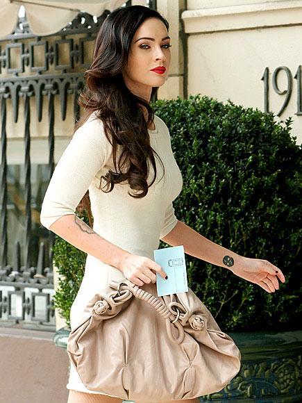 Megan Fox krem rengi örme elbisesi, kahverengi srilettoları ve pudra rengi çantasıyla harika görünüyor...
