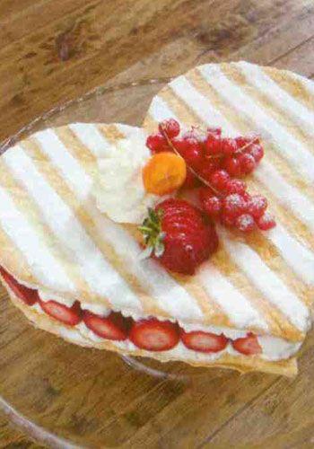Aşk pastası(4 kişilik)  Hazırlık süresi : 20 dakika  Pişirme süresi : 25 – 30 dakika  Malzemeler:  8 adet milföy  300 gr çilek  Kreması için:  250 gr süt  20 gr un  16 gr nişasta  2 yumurta sarısı  500 gr şeker  40 gr tereyağı  Vanilya  Süslemesi için: 1 yemek kaşığı pudra şekeri, 1 adet çilek, kırmızı orman meyveleri Hazırlanışı: Milföyleri 4'er adet olmak üzere 2 gruba ayırın ve bir merdane yardımı ile 25 X 25 cm ebatlarında inceltin. Her iki hamuru kalıp ya da kartondan çıkaracağınız bir şablon yardımıyla kalp şeklinde kesin. Fırın tepsisine pişirme kağıdı serin. Kalp şeklinde kestiğiniz milföyleri kağıtların üzerine alın ve kabarmalarını engellemek için bir çatal yardımı ile delin. 175 derecelik fırında altın sarısı renk alıncaya kadar, 20-25 dakika pişirin.   Kremasını hazırlamak için:Sütü kaynamaya bırakın. Yumurta, şeker ve vaniklyayı ayrı bir kapta karıştırın. Un ve nişastayı ilave edip tekrar karıştırın. Süte yumurtalı karışımı azar azar ilave ederek bir taraftan bir çırpma teli yardımı ile karıştırarak yedirin. Bir iki taşım kaynatıp ocaktan alın. Krema soğuyunca tereyağını ilave edip mikser yardımıyla çırpın.  Kremanın yarısını bir milföy katmanının üzerine yayın. Çilekleri ortadan ikiye kesin ve kremanın üzerine tekar krema dökün. Çileklerin üzerine tekrar krema dökün. Diğer milföy katmanını da üzerine koyarak elinizle hafifçe bastırın. Pastanızı pudra şekeri çilek ve kırmızı orman meyveleri ile süsleyin; buzdolabında 2 saat dinlendirdikten sonra servis edin.