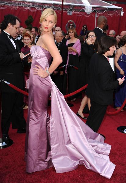 Charlize Theron John Galliano'nun Dior koleksiyoundan bu mor elbiseyle oldukça futuristik görünüyor. Göğüs hizasında iki gül şeklinde başlayıp kuyruk olarak biten açıkrenkli kısım ise ilgi uyandırıcı.