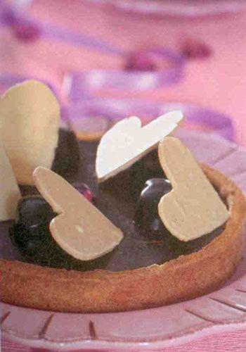 Çikolatalı tart (4 kişilik)  Sable hamuru için:  300 gram tereyağı  2 çay bardağı pudraşekeri  4 su bardağı + 2 çorba kaşığı un  1 çay bardağı toz badem  1 çay kaşığı toz vanilya  1 adet yumurta akı  Çikolatalı ganaş için:  250 gram krema  1 çorba kaşığı glikoz  200 gram bitter çikolata  25 gram tereyağı  Süslemek için: 100 gram beyaz çikolata  Yapılışı: Hamuru hazırlamak için, tereyağı ve pudraşekerini bir kaba alıp elinizle 1-2 dakika yumuşayana kadar karıştırın. Üzerine un, toz badem ve toz vanilyayı ilave edip karıştırmaya devam edin. Yumurta akını ekleyip 1-2 dakika daha yoğurun. Hamuru bir merdane ile açıp tart kalıbına, kenarları da kaplayacak şekilde yerleştirin. Önceden ısıtılmış 170 derce fırında 15 dakika pişirin.   Çikolatalı ganaş için, krema ve glikozu ocakta ısıtın. Küçük parçalar halinde kırdığınız çikolatanın üzerine döküp erimesini sağlayın. Akrışım ılınınca tereyağını ilave edip karıştırın. Pişirdiğiniz tartın içine doldurup buzdolabında soğutun. Yağlı bir kağıda kalp şekilleri çizin. Beyaz çikolatayı benmari usulü eritin ve kalp şekillerinin üzerine dökün. Soğuyunca tartınızın üzerine koyarak servis yapın.   Aşçının notu: Glikozu aktarlarda bulabilirsiniz.