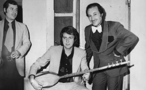 ÜMİT TOKCAN- MUSTAFA SAĞYAŞAR  Bir gazino kulisi. Ümit Tokcan, yine sazını eline almış, aynı gazinoda sahneye çıkan arkadaşı Mustafa Sağyaşar'a yeni derlediği türküsünü dinletiyor (1976).