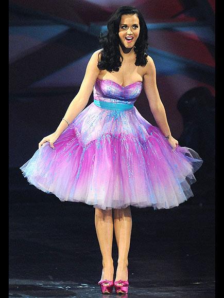 Gecenin bol ödüllü yıldızlarından Katy Perry neon ışıklarla süslü straplez bir Betsey Johnson elbise giyiyor.