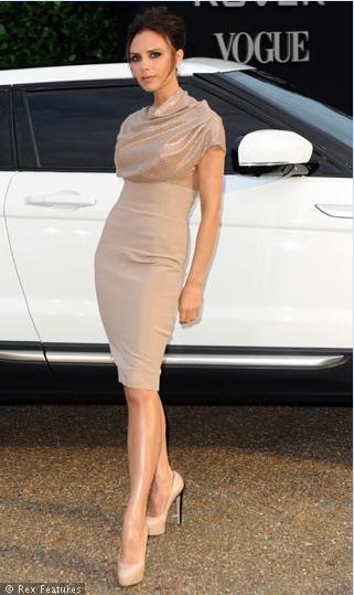 Victoria krem rengi elbisesiyle çok hoş bir görüntü sergiliyor.