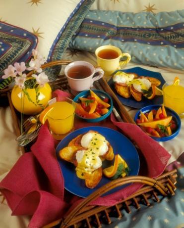 Şimdi yumurtayla buluşma zamanı: • Tavanızı yağlayın. Suyu, sirkeyi ve tuzu ekleyip kaynatın. Ateşi kısın, yumurtaları tek tek minik bir kabın içinde kırın ve yavaşça tavadaki suya akıtın.  • Aşağı yukarı üç-dört dakika sonra yumurta beyazları katılaşmaya başlayacaktır. Bir spatulayla çıkartıp kenara koyun.  • Sırada ekmekler var: İngiliz Muffin ekmeğini bulamayabilirsiniz. O zaman önerimiz, bazı restoranlarda da sunulduğu gibi hamburger ekmek dilimleri olacaktır. Sadece kenarlarını hafifçe kesmeniz lazım.  • Ekmeklerinizin üzerine tereyağı sürün. Üstüne önceden tavada ısıttığınız domuz pastırmasını yahut dana jambon dilimlerini (hangisini tercih ediyorsanız) yuvarlak haline getirip oturtun.  • Hazır bekleyen yumurtalarınızı üstüne koyun ve ılık Hollandaise sosunu da en üste ilave edip lezzetin keyfini çıkartın.   Servis Önerisi: Rendelenmiş Frenk soğanıyla süsleyebilirsiniz. Görüntü şıklaşıyor, tat artıyor.