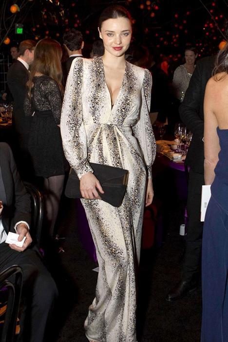 Miranda Kerr Çiçeği burnunda anne Miranda Kerr, derin göğüs dekolteli be yüksek omuzlu elbisesiyle çok şık görünüyor.