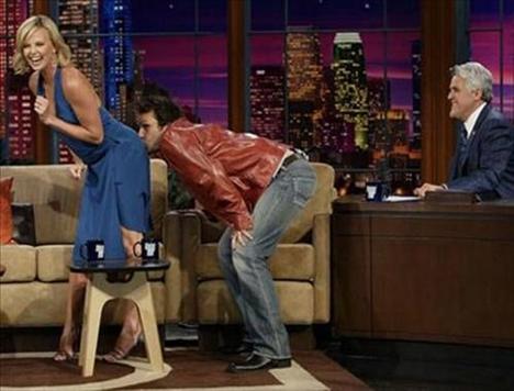 2005 senesine ait bir Jay Leno şovunda, Dane Cook , Charlize Theron'un poposunu öperken.