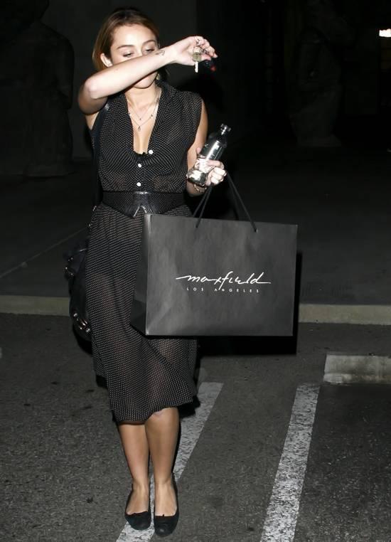 Genç yıldız Miley Cyrus, transparan elbisesi ve elindeki alışveriş çantasıyla otomobiline binerken flaşların azizliğine uğradı.