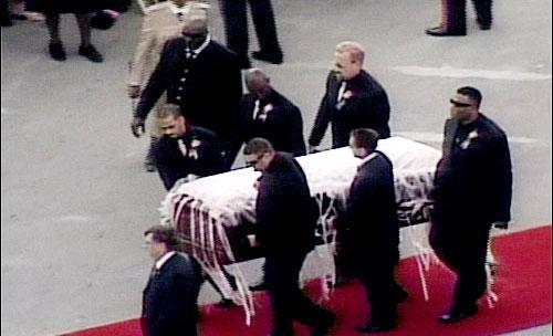 Kilise görevlileri tarafından karşılanan uçaktaki tabut törenle cenaze alanına götürülüyor.