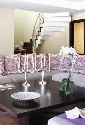 Katlar arası ahşap merdivenlerin kullanıdığı evin salon bölümünde renk olarak mor ve tonları tercih edilmiş.