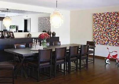 Duvarları açık renk olan salonda büyük ve ihtişamlı yemek masası dikkat çekiyor. Masanın hemen arkasında bulunan büfenin üzeri ise aile fotoğrafları ile süslenmiş durumda.