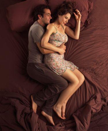 """Sarılıp sokulmak, mutlu bir beraberliğin işareti olan hareketlerdir fakat ya yatağınızın zıt taraflarını tercih ediyorsanız ya da aranızdaki mesafeler hep çok uçsuzsa?  Uyur, rüya görür, sevişir ve kucaklaşırsınız. Bir yatağı paylaşmak hakkında başka ne söylenebilir ki? Bilakis söylenecek çok şey var. Goodbye Insomia ve Hello Sleep kitaplarının yazarı Psikiyatr Samuel Dunkell uyku pozisyonlarını 25 seneyi aşkın bir süredir analiz edip, elde ettiği verilerle insanlar ve ilişkileri hakkında hiç bilinmeyen gerçekleri ortaya çıkarıyor. Seneler geçtikçe uyuma biçimlerimiz değişir, evrimleşir. Ama duygusal karmaşamızı da her zaman yansıtacaklardır. Eşiniz ve siz nasıl uyuyorsunuz? İşte farkında olmadan anlatılanlar:  Kaşık pozisyonu:   Çok yakın, çok güvenli bu resim evliliklerin/ilişkilerin ilk 3-5 senesinde karşılaşılan en genel pozisyondur. """"Genelde erkek kapsayıcı ve faaldir"""" diyor Dr. Dunkell. """"Kadın arkadan sarılma pozisyonunu benimsiyorsa, bu daha özveri gösteren taraf olduğuna veya daha fazla duygusal destek ihtiyacı içinde olduğuna işarettir."""" Kaşık pozisyonu, genital bölgenin arka kısımla bitiştiği cenin duruşu, tam olarak erotik bir his uyandırmasa da maksimum fiziksel yakınlığı sağlar. """"Çoğu çift kaşık pozisyonunu rahat ve güvenli bir koza olarak buluyor"""" diyor psikiyatr ve terapist Dr. Shirley P. Glass. Evliliğin ön safhalarında çiftler bu pozisyonu, gecenin büyük bir bölümünde birbirleriyle eşleşerek korurlar. """"Çiftten biri döndüğünde, diğeri de dönüp ona sarılır. Öylece kaşık pozisyonu ters taraftan devamlılığını sağlar"""" diyor Dr. Dynkell. Fakat uzun süreli bir evliliğinizin olması bu yakınlığı kaybetmeniz gerektiği anlamını taşımaz..."""