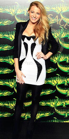 Blake Versace for H&M mini elbise ve siyah bir blazer ceket giyiyor.
