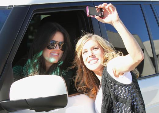 Khloe Kardashian kırmızı ışıkta yayına gelen bir hayranıyla fotoğraf çekirirken.