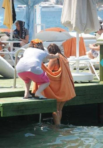 Tanyeli, görüntülenmek istemediği için denizden çıkarken hemen havlusuna sarındı.