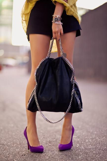 Zincirli siyah renk çantanızı renkli bir ince topluklu ayakkabınızla kombinleyebilirsiniz.