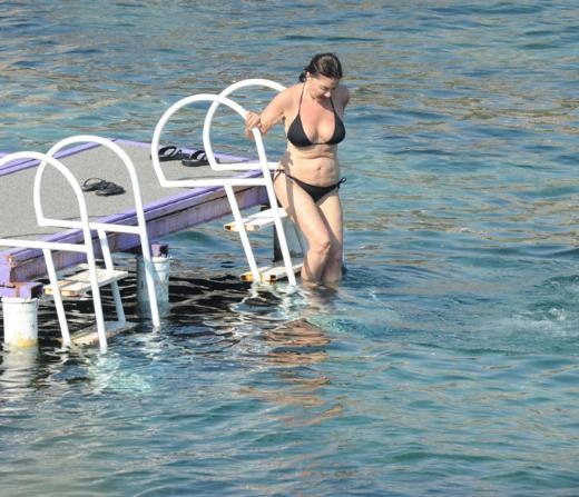 Üzerine siyah bikinisini giydi ve hemen plaja koştu