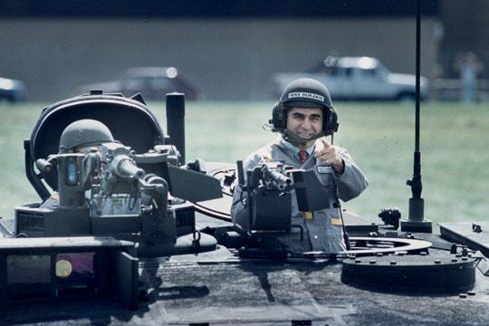 Michael Stanley Dukakis   ABD'li demokrat politikacı, eski Massachusetts valisi ve 1988 ABD başkanlık seçimleri'nde demokrat başkan adayı. Dukakis ile Baba Bush arasında geçen seçim kampanyasının climax'i 13 Eylül 1988'de Dukakis'in bir M1 tankını sürerken çekilen reklam filmi...  Bush'un, kendisini askeri harcamalarda hep muhalefet yaptığı için Amerika'yı savunmada zayıf düşüreceği iddiasına karşılık, Dukakis, Demokratların savunma harcamalarında önemli bir tavrı olduğunu söylemekte ve bunu ispat etmek için de, tank kullanırken yer aldığı bir reklam filmi çekti. Ancak başkan adayınını bu fotoğrafı imajı üzerinde pek olumlu bir etki bırakmadı.