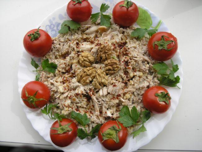 Sebzeli Çerkez Tavuğu  Malzemeler:  1-1,5 kg'lık tavuk (temizlenip, tüyleri ütülenmiş), 1 pırasa (püskülü ve yeşil kısmı kesilip alınmış), 1 havuç (hafifçe kazınmış), 1 küçük kereviz (hafifçe kabuğu soyulup 4'e bölünmüş), 1 soğan, 1 defne yaprağı, 1 çorba kaşığı tuz, 20 su bardağı su, 2 dilim ekmeğin içi, 1/2 su bardağı süt, 250 gr ceviz içi (iki kez çekilmiş), 4 ceviz içi (ikiye bölünmüş), 1/2 kahve kaşığı kırmızı biber   Hazırlanışı:  Büyük bir tencereye 20 bardak su, tavuk, pırasa, havuç, kereviz, soğan, defne yaprağı ve 1 çorba kaşığı tuzu koyarak harlı ateşte kaynatınız.  Su kaynar kaynamaz ateşin altını kısarak ağır ateşte tavukları 2-2+1/2 saat pişiriniz.Tavuklar pişince tenceredeki suyu bir süzgeçten geçirerek süzüp kenara koyunuz. Haşlanmış sebzeleri atıp, tavuğu ayrı bir tabağa alınız.   Sosu için bir kapta ekmek içini sütle ısıtınız. Bir başka tencerede çekilmiş cevizin yarısı ile kırmızı biberi karıştırarak ağır ateşte 3-4 dakika ısıtınız. Isıtılmış ceviz ve biber karışımını bir tülbente alıp sıkarak, cevizin yağını bir küçük kaba çıkarınız. Sütle ıslatmış olduğunuz ekmek içlerini sıkıp geri kalan ceviz ve tuzla birlikte bir kaba koyup tülbentte kalmış olan malzemeyi de ekleyerek, yumurtateliyle iyice çırpınız. Başlangıçta süzmüş olduğunuz tavuk suyundan 1+1/2 subardağı alıp çırpmaya devam ederken bu sosa yediriniz.   Tavuğun derisini ve kemiklerini ayıklayınız; parçalarını ince olarak dilimleyip servis tabağına yerleştiriniz. Üstüne sosu ve ceviz yağını dökünüz. İkiye bölünmüş ceviz içleriyle süsleyip soğuk olarak servis ediniz.   Not: Çerkez tavuğunu, tavuğu sonunda 1 su bardağı tavuk suyuyla yeniden ısıtıp suyunu süzdürerek ve üstüne sosunu çok az ısıtıp dökerek, sıcak olarak da servis edebilirsiniz.