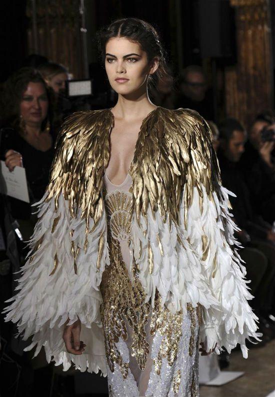 Altın rengi detaylı, omuz bölgesi ve kolları kuş tüyleriyle bezenmiş bu elbise çok şık duruyor.