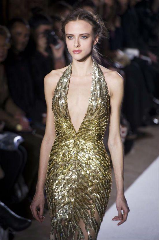 Göğüs dekolteli altın rengi model bu sezon giyilecek elbise formları arasında yer alıyor.