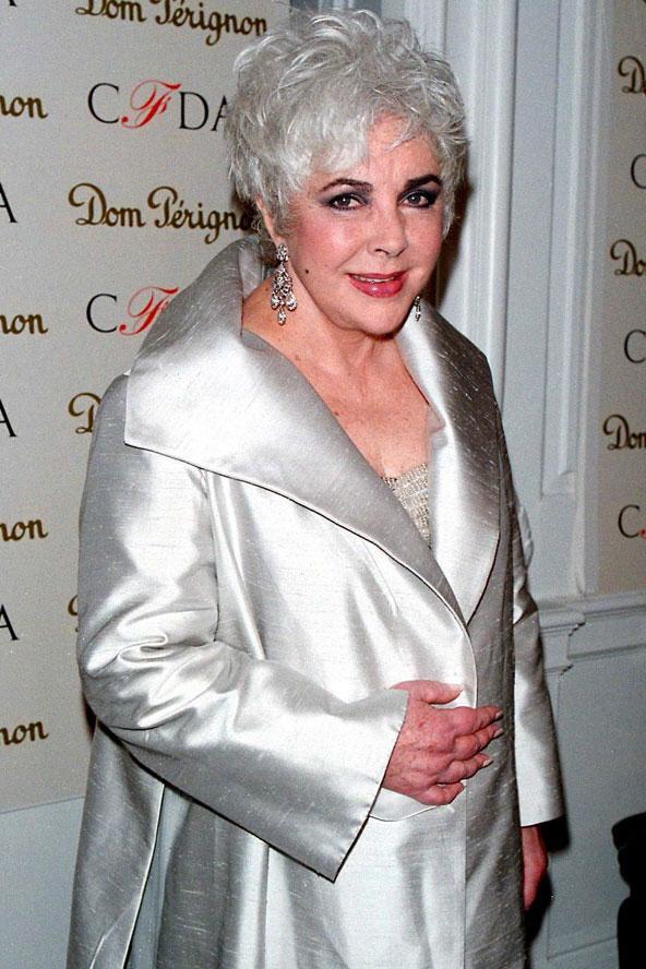Elizabeth Taylor kamera karşısına son çıkışlarından birinde daha sade bir stili benimsemiş görünüyor. Yine de parlak kumaşlar, eyeliner ve kısa saçları ünlü yıldızın vazgeçilmezleri arasında yerini alıyor.  Moda Kanalları Editörü: Burcunur YILMAZ