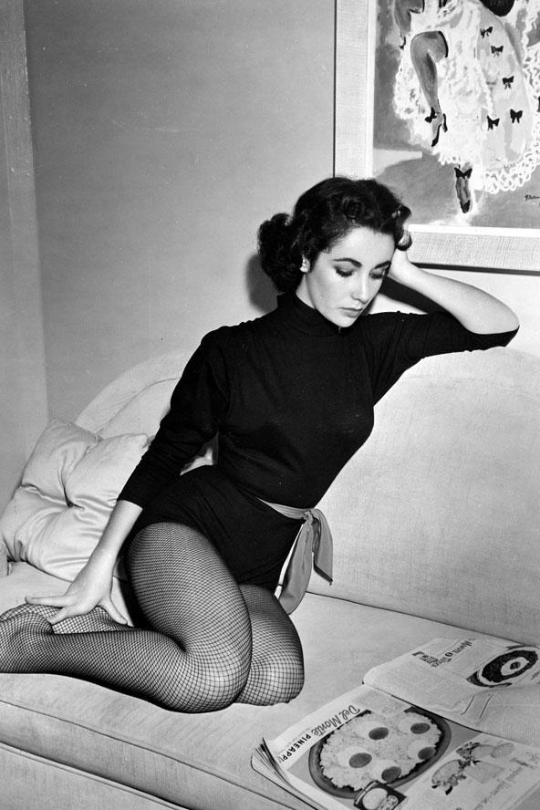 File çorapları, balıkçı yaka bir kazağı ve eyelinerı sadece Elizabeth Taylor bu kadar zarif gösterebilir. Güzel yıldız bir fotoğraf çekimi için siyahlar içinde gazete okurken görünüyor.