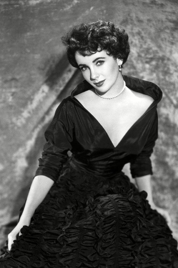Cazibeli görünüm dedikleri bu olsa gerek. Elizabeth Taylor siyah Christian Dior tuvaleti içinde çok zarif görünüyor. Derin V yakalı ve kabarık etekli bu elbise, Taylor'ı prenses gibi göstermiş. Üstelik tek sıra inci kolyesi de mükemmel bir seçim.