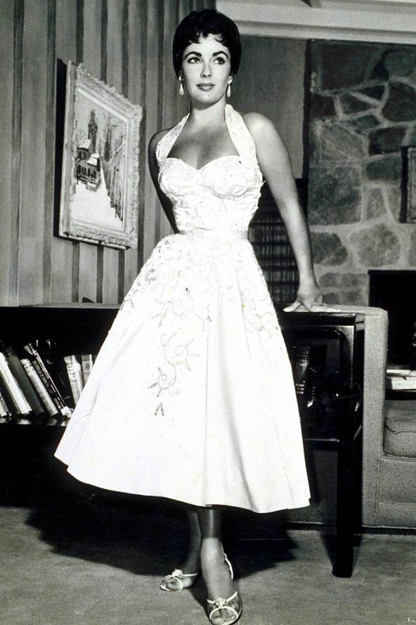 1950'li yıllar'ın ikonik görünümlerinden birini daha da mükemmel hale getirmiş Liz Taylor... Vücudu saran boyundan bağlı elbisesi, ince kemeri ve kabarık etekleri ile tam bir poster kızı görünümünde...