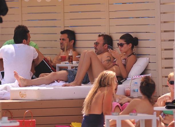 Gazetecilerin fotoğraf çektiğini gören Sergen Yalçın, güneşlenen kız arkadaşının bacaklarını havluyla örttürdü.