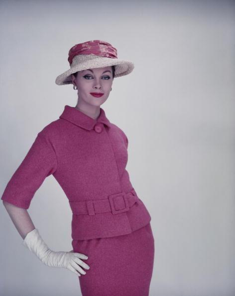 1955 yılına ait bir moda çekimi ve o yılların en trend kıyafetlerinden etek ve kısa kollu ceketi, yine onlarla aynı renkte olan pembe hasır şapkayla tamamlamış bir model.