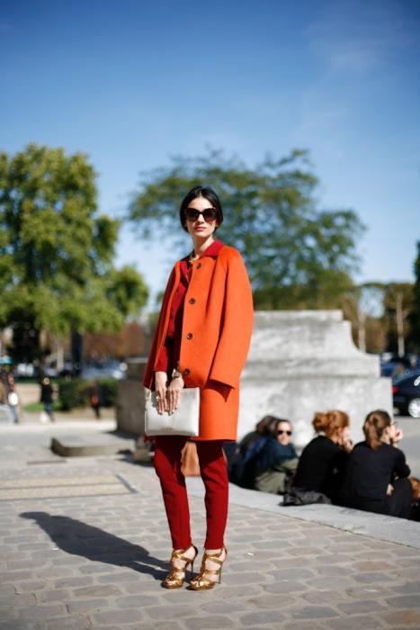 Kırmızı pantolonla uyum sağlamış turuncu palto