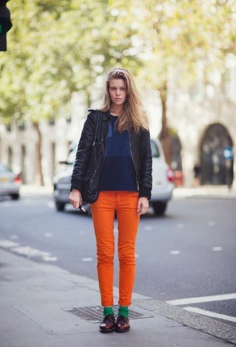 Siyah deri ceketle uyum sağlamış turuncu pantolon