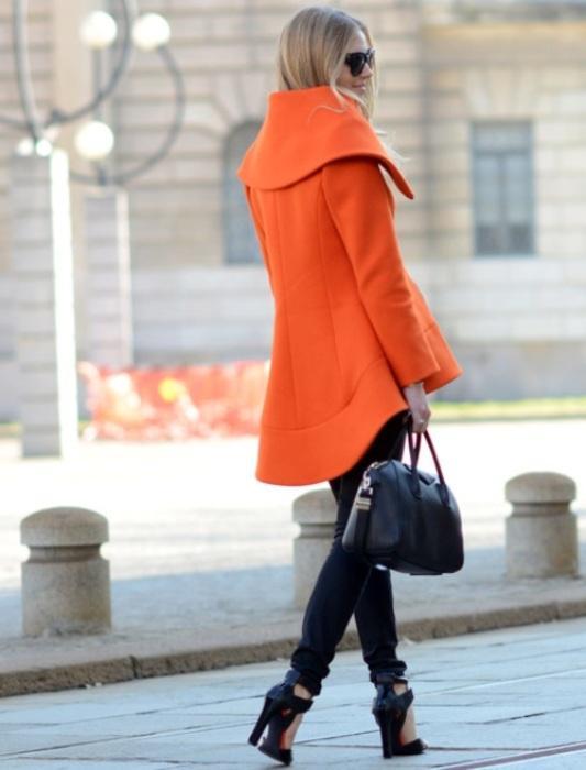 Siyah pantolonla uyum sağlamış turuncu kaban