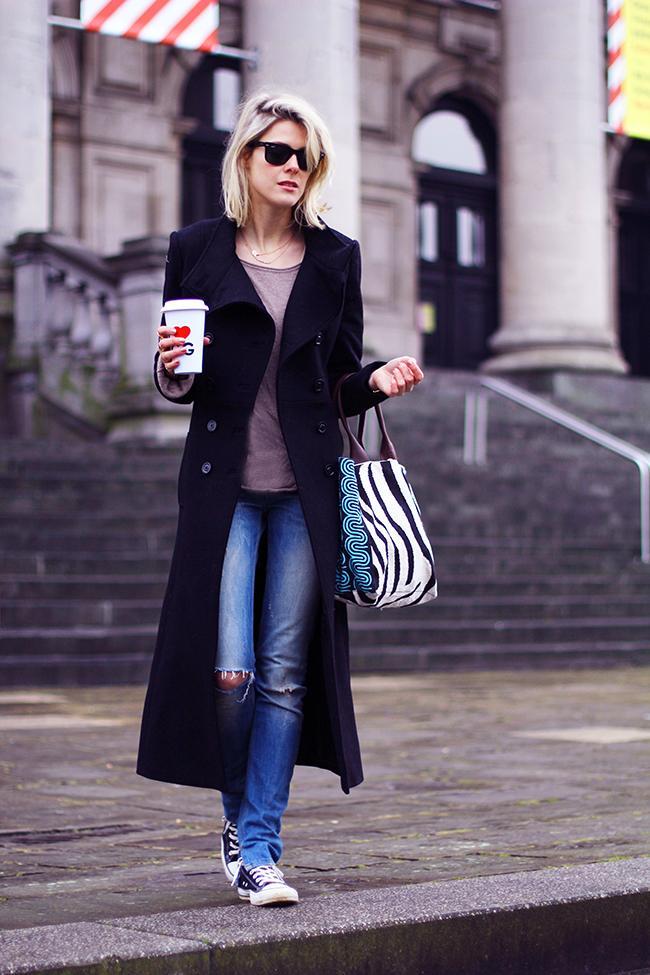 Kot pantolonun üstüne giyilmiş uzun siyah palto ve altına giyilmiş mavi converse gayet rahat şık bir görüntü sağlamış