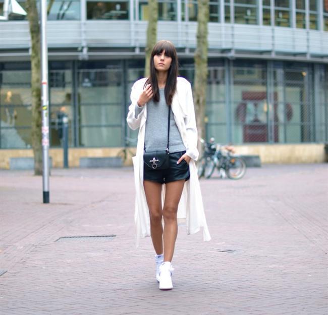Şortun üstünde giyilmiş uzun beyaz palto ve altına giyilmiş beyaz spor ayakkabı alışverişe çıkmak isteyen kadınların tercih etmesi gereken bir kombin