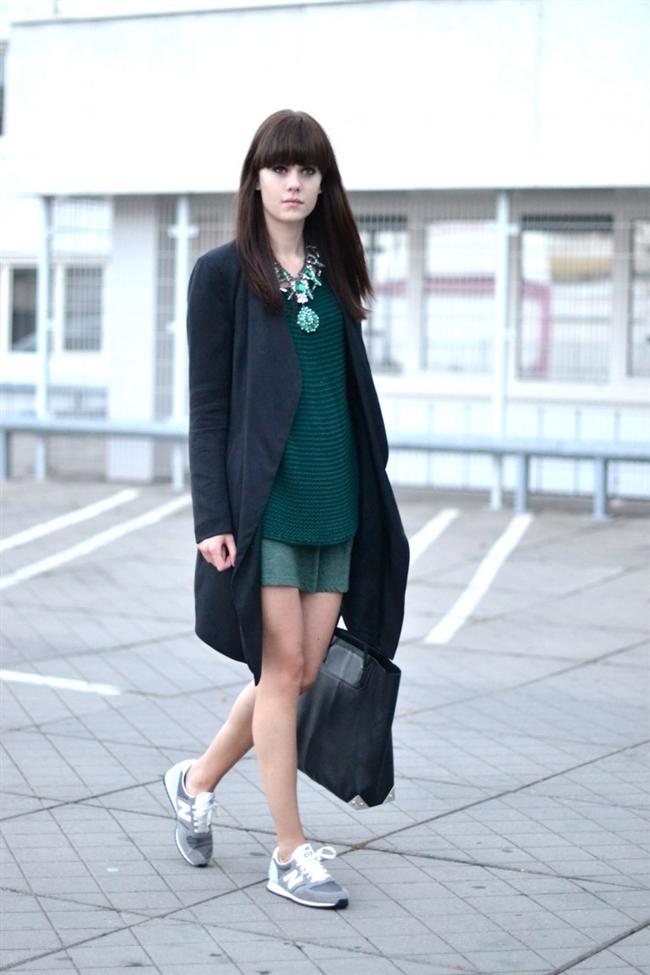 Mini eteğinin üstüne giyilmiş siyah palto ve altına giyilmiş spor ayakkabı uyum içinde