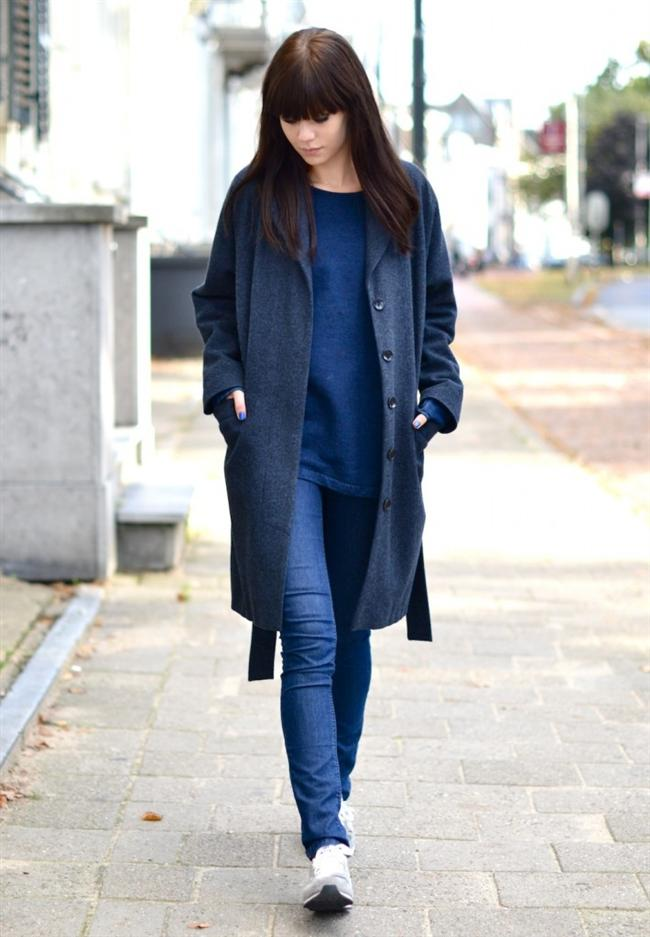 Kotun üstüne giyilmiş füme uzun palto ve altına giyilmiş gri spor ayakkabı kadınların gündelik hayatlarında kullanabilecekleri bir kombin
