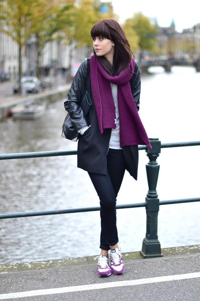 Dar paça siyah pantolonun üstüne giyilmiş siyah palto ve altına giyilmiş mor spor ayakkabı gezmeye çıkmak isteyen kadınların tercih etmesi gereken bir kombin