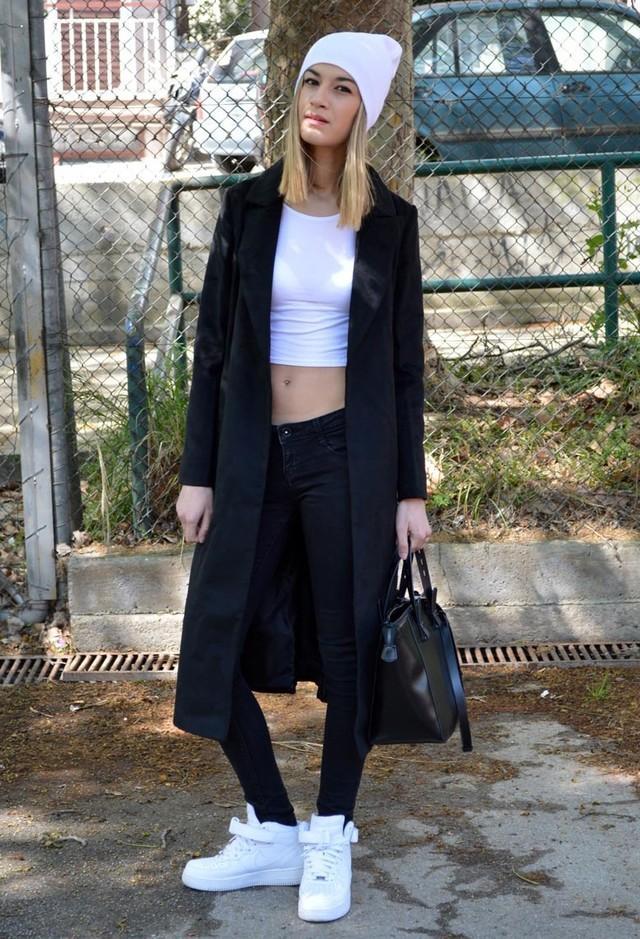 Siyah dar paça pantolonun üstüne giyilmiş uzun siyah palto ve altına giyilmiş beyaz spor ayakkabı günlük şıklık için ideal bir görüntüde