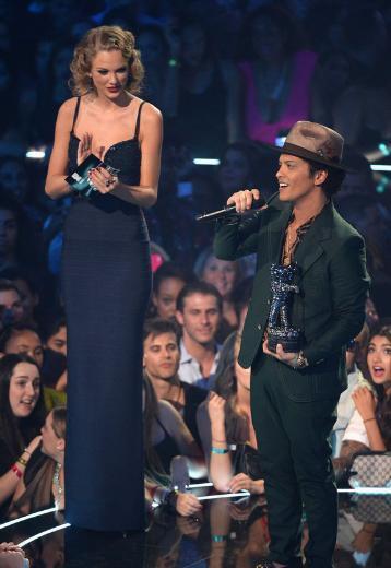 Bruno Mars, 1.65 cm boyunda. Bir ödül töreninde topuklu ayakkabı giymiş 1.78'lik Taylor Swift'in yanında böyle görünüyordu.