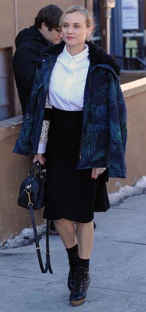 """Bu hafta """"Kim Ne Giydi?"""" bölümünde Diane Kruger'ı ele aldık. Ünlü oyuncu,  sade şıklığı tercih etmiş ancak klasik parçaları modern detaylarla zenginleştirmiş. Yüksek bel etek içine sadece ince bir beyaz gömlek giyen Kruger'ın, omuzlarına gelişigüzel atılmış parkasıyla yakaladığı bu stile bayıldık. Galerimiz içerisinden ünlü oyuncunun üzerindeki kıyafet ve aksesuarları satın alarak siz de aynı stili yakalayabilirsiniz. Hadi sizin için seçtiğimiz parçalara bir göz atın..."""