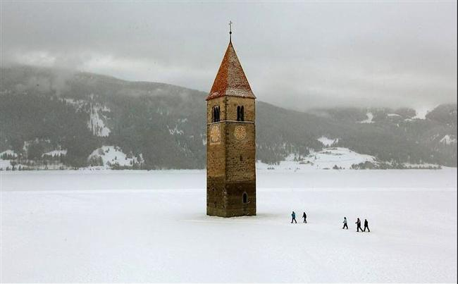 Donmuş bir gölde yükselen kilise kulesi, Reschen, Italy