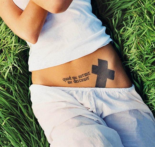 """3. Haç Dövmesi  Angelina Jolie'nin en popüler dövmelerinden biriside haç dövmesidir. Kasığının üstüne yaptırdığı bu dövmesinin Jolie'ye çekicilik katığı konusunda birçok insan hem fikirdir. 1995 yılında Johnny Lee Miller'la evlenmeden bir gün önce yaptıran Jolie, """"Tamamen sembolikti. Ve kötü bir şeyi değil iyi bir şeyi"""" dedi. Bu dövmesi karnının alt tarafında Latince bir deyimle bir araya gelmiştir. """"Quod me nutrit me destruit"""" deyiminin olduğu bu dövmenin anlamı """"Beni besleyen şey, beni yok eder"""" dir."""