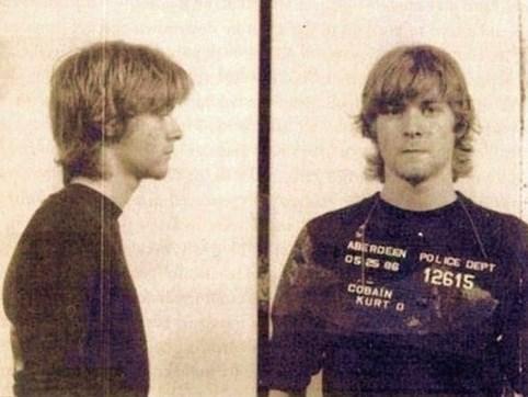 """15.  19 yaşındaki Kurt Cobain'in polis kayıtlarındaki bir fotoğrafı. (1986)  Sprey boya ile arabaların üzerine """"God is gay"""" yazdığından dolayı tutuklanmış."""