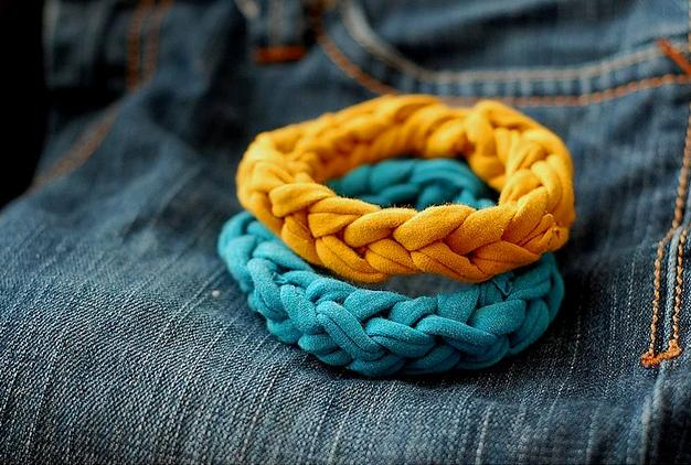 Çantadan sonra rengarenk bileklikler yapmak istemez misiniz?  Tişört kumaşı esnek olduğundan bilekliklerinize değişik bir doku katacaktır. Yapacağınız şey çok kolay. Tişörtünüzden birkaç şerit kesin ve örgü yapın. Bu örgüyü iki ucundan birleştirin işte hazır.