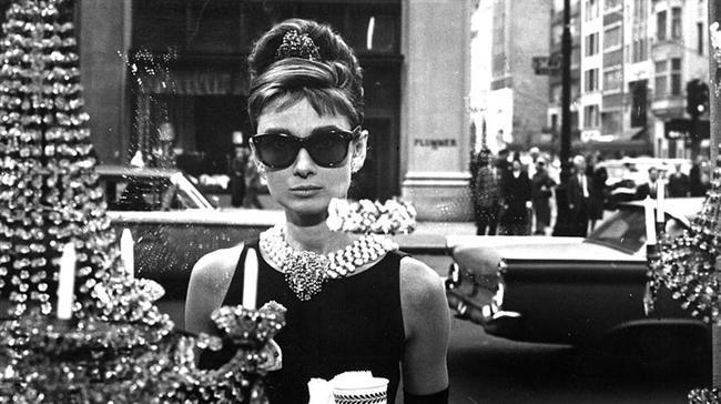 """3. Tiffany'de Kahvaltı/ Breakfast At Tiffany's (1961)  Hayatta tutunamamış iki kaybeden insanın dokunaklı aşk hikâyesinin anlatıldığı """"Tiffany'de Kahvaltı"""", aslında yüzeydeki öforinin neşe ve havailiğin altında yatan derin bir mutsuzluğu örttüğü karamsar bir romandır. Roman adını New York'ta bulunan ünlü ve tarihi bir mücevher dükkânı olan Tiffany's den alır. Romanın kahramanı Holy ne zaman karamsarlığa kapılsa, günün hangi saatinde olursa olsun, soluğu bu mücevhercinin vitrininin önünde alır, ayaküstü kahvesini içip sadviçini yerken pırlantaları seyreder. Böylelikle depresyonundan kurtulmaya çalışır. Bu mağaza temsil ettiği zenginlik ve dinginlikle Holy'e sükunet veren tek şey olmuştur artık (daha önce uyuşturucuyu bile denemiş faydası olmamıştır)."""